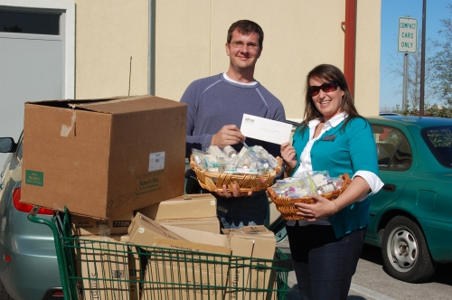 Native Sun staffer Michael Drinkwater hands off over $2500 in product and donations raised by Native Sun customers for the Sulzbacher Center.