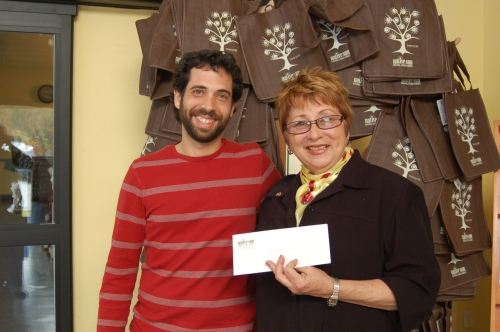 Aaron hands off the January GreenApples donation check to Helen Werkings, Executive Director for Memories of Love.